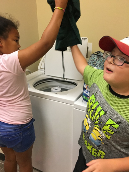 Lighthouse Summer Transition Program youth doing laundry