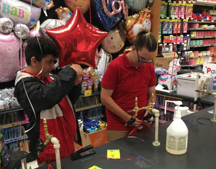 Lighthouse Summer Transition Teens blow up balloons behind counter at store